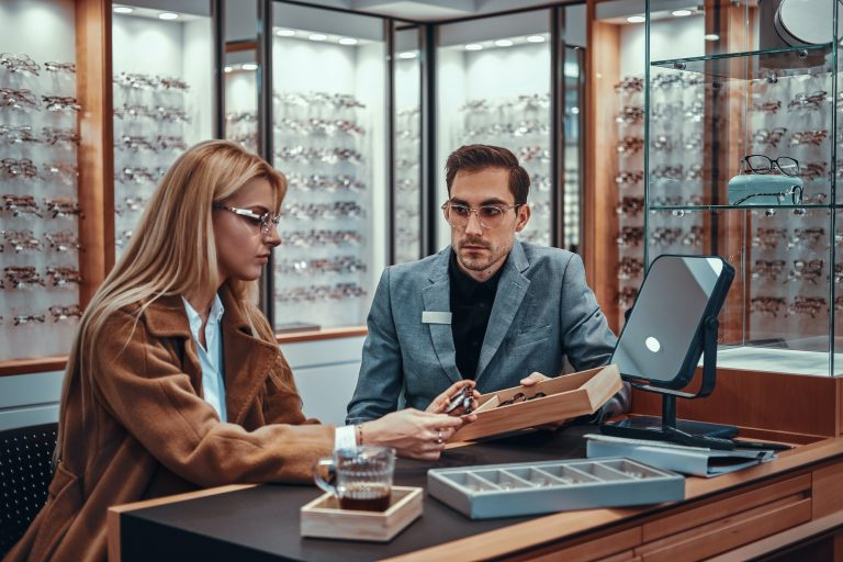 Lady is choosing new glasses at store