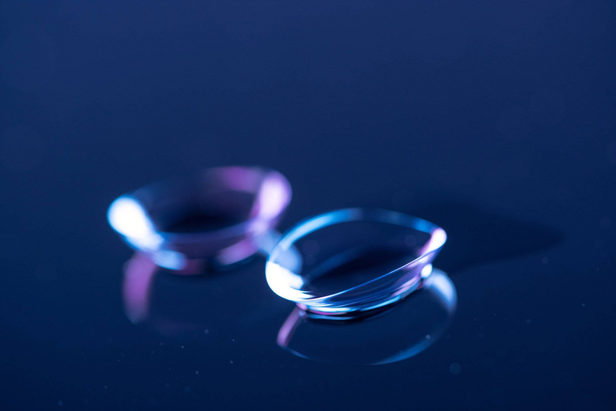 selective focus of contact lenses arranged on blue backdrop